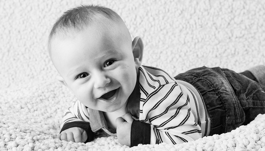 Beautiful image of happy, smiling baby in black and white. Photograph by Emotion Studios.