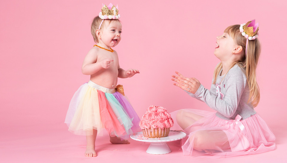 Giggling sisters in a cake smash shoot at Emotion Studios of Shropshire