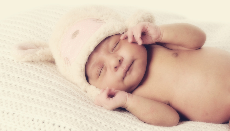 Cute picture of baby sleeping in hat. Image by Emotion Studios.