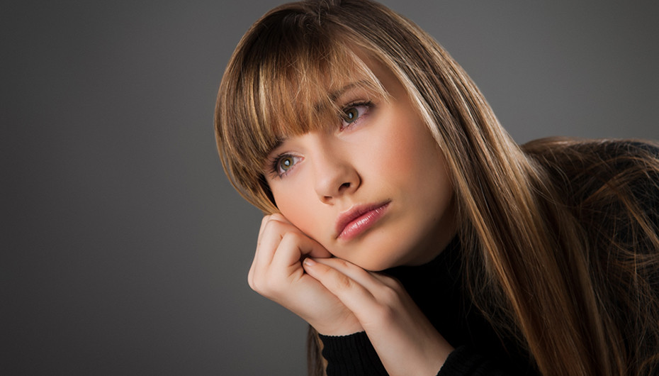 Stunning photograph of girl looking away from camera against grey background. Picture taken by Emotion Studios.