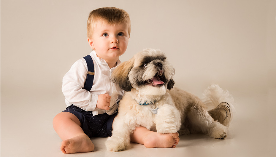 Image of a child cuddling with pet dog, photographed by Emotion Studios.