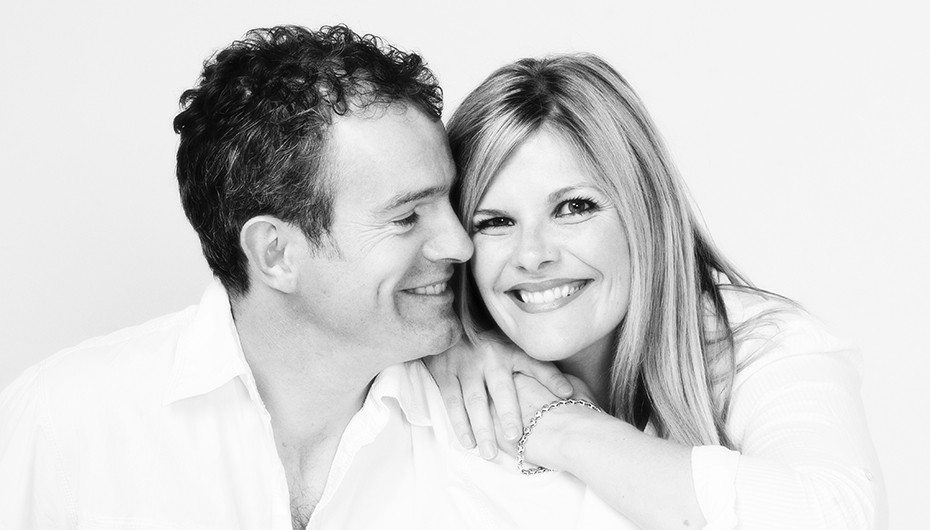 Photograph of a happy couple smiling. Image in black and white, photographed by Emotion Studios.