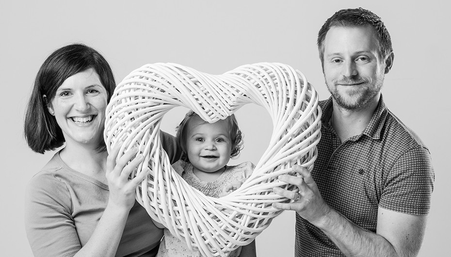 Adorable family portrait in black and white with heart prop. Photograph by Emotion Studios.