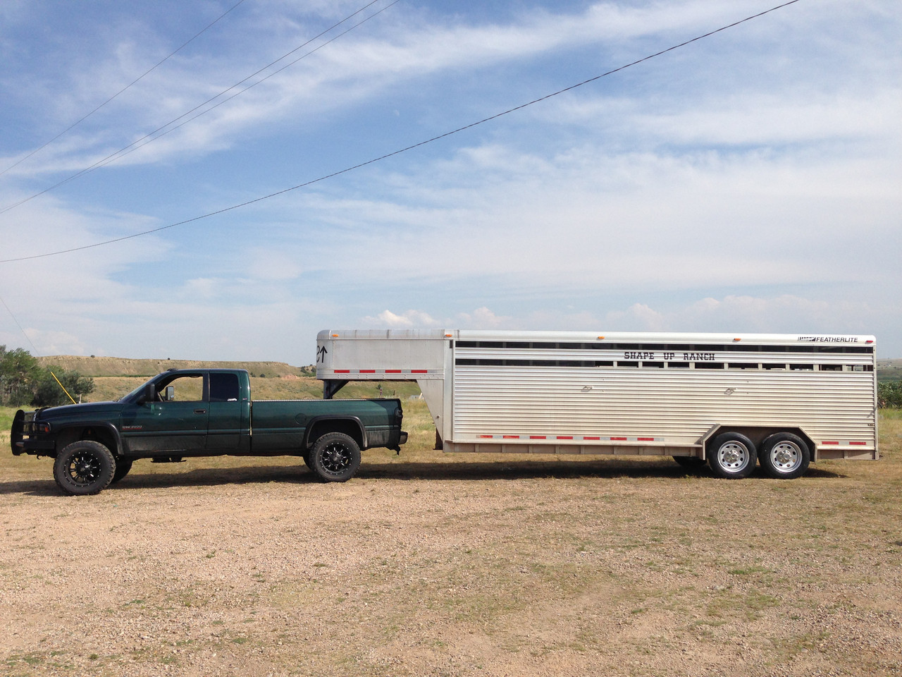 Dodge 2500 pulling Featherlite livestock trailer with Boar Evron rims.