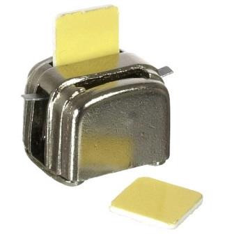 Silver toaster with in piece of bread in a slot and one piece alongside the toaster