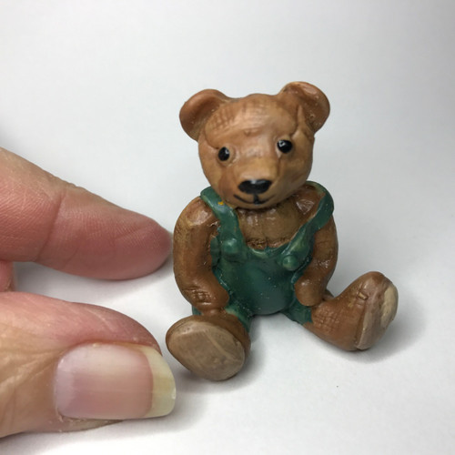 Itty bitty brown bear wearing green overalls