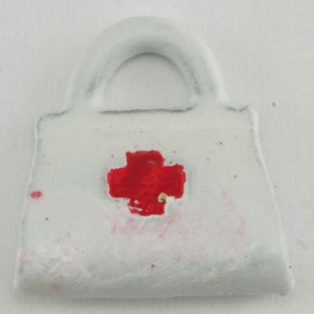 Tiny white painted metal nurse's bag with red cross