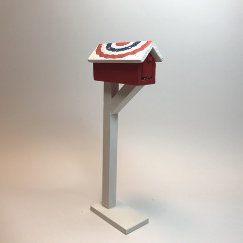 Red mailbox with patriotic bunting covered roof
