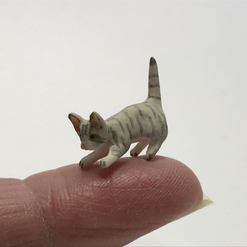 Pouncing gray dollhouse miniature kitten on finger (for scale)