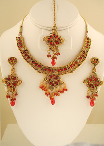 Intricate designed set with pear shaped Red & clear stones set against gold background
