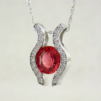 You will be captivated by this modern, elegant 14 karat White Gold Sapphire and diamond pendant. Yes, we said Sapphire. They do come in every color, and this 1.36ct. bright cinnamon orange Sapphire is a fine example of the orange variety. Framed with .33ct. T.W. of Ideal cut Diamonds, and includes a 1mm 14 karat White Gold anchor chain, 16 inches long.  Designed, and created in our studio by the artist Stuart J.