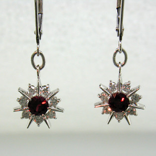 You will be the star with these sparkling 14 karat White Gold Ruby and diamond earrings. Set with two brilliant deep red Rubies, and .28ct. T.W. of Ideal cut Diamonds, dangling on lever backs. These earrings look like snowflakes, but sparkle like stars, so we call them Starflakes(tm), and they measure 1 inch long.    Designed, and created in our studio by the artist Stuart J.