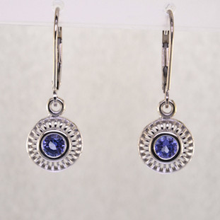 Blending traditional and modern design, these earrings dazzle, day or night. Handcrafted in 14 karat White Gold with sparkling 4mm Tanzanite gemstones, dangling on lever backs. Earrings measure 1 inch long.    Designed, and created in our studio by the artist Stuart J.