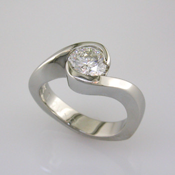 This beautiful engagement ring design with its simple, clean lines captures the diamond perfectly. The bottom has soft rounded corners for the ultimate comfort. This is a classic, timeless design.  This elegant engagement ring is priced in 14k gold, and can be made in any karat or color of gold, and in platinum. This one is made for a 1 carat center (priced seperately), but we can make it for any size. A matching shadow wedding band is also available.  This custom designed engagement ring is individually crafted to be Perfectly You, and takes about 2 weeks to create. Call us for more information about how we can customize this design Just For You. Designed, and created in our studio by the artist Stuart J.