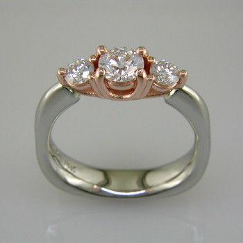 This delicate 3-stone ring is magical. 14 karat White Gold ring shaped with a soft square at the bottom, and 14 karat Rose Gold woven prong work on top. It feels soft and comfy on your finger. Set in the center is a 1/2 carat Ideal cut Diamond, and the sides total .34ct T.W. Ideal cut Diamonds.  Finger size 6 1/2. Can be sized, or custom made in your size.  Designed, and created in our studio by the artist Stuart J.