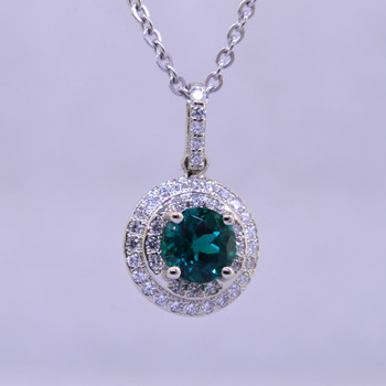 Elegant and timeless double halo pendant, in 14 karat white gold with .33ct. T.W. of Ideal cut diamonds, and an incredible 6.5mm deep green, brilliant cut Chatham Created Emerald. Includes a 1.3mm diameter 14 karat white gold wheat chain, 18 inches long.  Designed, and created in our studio by the artist Stuart J.  Chatham® Created Gemstones are grown in carefully controlled laboratory conditions. They are chemically and optically identical to their natural counterparts, yet cost much less. Because the environment in which they are grown is controlled, the imperfections often found in natural gemstones, are absent in Chatham® Created Gemstones. Because of this, and superior cutting, Chatham® gems exhibit the color and sparkle of the finest natural gems. Each one comes with a Certificate of Authenticity, and a Lifetime Warranty.