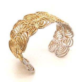 This delicate yet sturdy cuff bracelet showcases a striking flower motif, and is crafted in rich yellow gold plated Sterling Silver. Great style for any occasion. Bracelet measures 1 1/4 inches wide.  Handcrafted in Northern Spain.