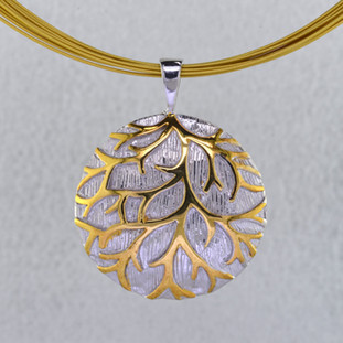Gold branches stand out against a wintery white background in this nature inspired Sterling Silver pendant. Hanging on a 12 strand gold plated stainless steel wire necklace, 16 inches long. The pendant measures 1 1/4 inches around, for a distinctive look.  Handcrafted in Northern Spain.