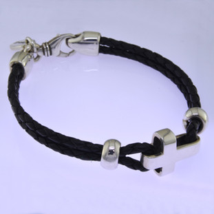 For the man who is edgy, strong, and spiritual. Hand-crafted in braided black Leather with a Sterling Silver cross, and a bold Sterling Silver clasp. Measures 8 inches long.  by David Heston of San Rafael, California.