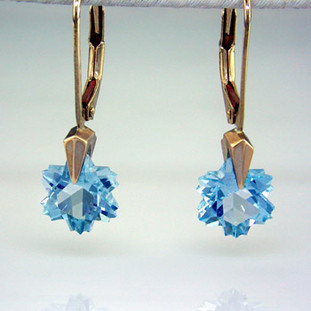 What's better than one sparkling snowflake? Two, of course. One for each ear. And you can turn up the heat, because these snowflakes won't melt. Exclusively ours, each blue topaz snowflake is custom cut just for us, in Canada, by master gem cutters. Each snowflake measures 10mm, and dangles in a 14 karat white gold Piercette® setting on a lever back, measuring 1 inch long.  Designed and handmade by the artist Stuart J.  A Piercette® is a patented method of setting, with a gemstone that moves. The gem is set so that it swivels with every movement of the wearer, exhibiting extra sparkle.