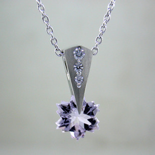 "This Lavender Amethyst snowflake and Diamond Piercette® pendant will melt your heart. Dangling in 14 karat white gold, with an 8mm custom cut light lavender Amethyst snowflake and sprinkled with .07ct. T.W. Ideal cut Diamonds. The Amethyst snowflake gemstone is custom cut, exclusively for us, in Canada. Includes a 14 karat white gold 1.0mm smooth snake chain, 18 inches long. Pendant measures 5/8"" long.  Designed and handmade by the artist Stuart J.  A Piercette® is a patented method of setting, with a gemstone that moves. The gem is set so that it swivels with every movement of the wearer, exhibiting extra sparkle."
