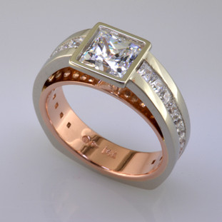 This contemporary diamond engagement ring will really make you feel special, and can be made in gold or platinum, or both. Feel modern, elegant, and cool when wearing this diamond engagement ring. Shown in 14 karat white and rose gold, with 1.10ct. of ideal princess cut diamonds, and a 6mm princess cut center (priced separately). This diamond engagement ring is great for professionals who work with their hands, because there are no prongs to catch.   This custom designed diamond engagement ring is individually crafted, to be Perfectly You, and takes about 3-5 weeks to create. Call us for more information about how we can customize this design Just For You. Designed, and created in our studio by the artist Stuart J.