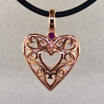 See the excitement on her face when you give her this beautiful vintage heart pendant. Lovely filigree heart in 14 karat rose gold, accented with a deep red genuine ruby. This dynamic heart measures 1 inch long, and hangs on a 2mm black leather cord.  Designed and handmade by the artist Stuart J.