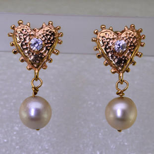 For the gal who loves the nostaligic feel, these one of a kind pearl heart earrings have a vintage feel, with 14 karat yellow gold ornate hearts and beautiful antique ivory pearls that dangle from the bottom. The hearts each have a 3mm cubic ziconia accent in the center, with posts. Measures 1 inch long.   Made by an unknown artist, and lovingly restored by Stuart J.