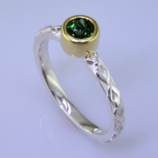 This cool, hip, and fun stackable ring is the start of your new collection. This ring will have many different looks when you stack it with other rings, or enjoy it alone in your everyday style. Hand finished in Sterling sliver with an 18 karat yellow gold bezel holding a beautiful 4.5mm round green tourmaline. Finger size 7. We will make this in any size you need in about ten days. Designed, and created in our studio by the artist Stuart J.  This ring is also shown in other gemstone colors and sizes, which are sold separately, and can be stacked with all other rings in our stackables collection. You can also stack it with any ring you like. There are no rules. Call us with your favorite color, and we will customize this Just For You.
