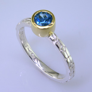 This cool, hip, and fun stackable ring is the start of your new collection. This ring will have many different looks when you stack it with other rings, or enjoy it alone in your everyday style. Hand finished in Sterling sliver with an 18 karat yellow gold bezel holding a beautiful .65ct.round blue topaz. Finger size 7. We will make this in any size you need in about ten days.  Designed, and created in our studio by the artist Stuart J.  This ring is also shown in other gemstone colors and sizes, which are sold separately, and can be stacked with all other rings in our stackables collection. You can also stack it with any ring you like. There are no rules. Call us with your favorite color, and we will customize this Just For You.