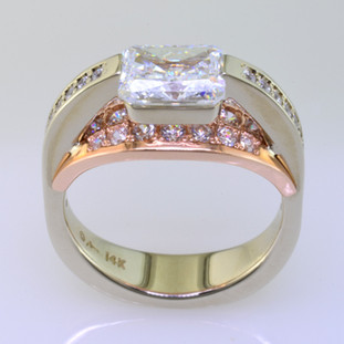 This contemporary diamond engagement ring will really make you feel special, and can be made in gold or platinum, or both. Feel modern, elegant, and cool when wearing this diamond engagement ring. Shown in 14 karat white and rose gold, with 73ct. of ideal round cut diamonds cascading down both sides and a 1.00ct. fancy radiant cut center (priced separately). This diamond engagement ring is great for professionals who work with their hands, because there are no prongs to catch.   This custom designed diamond engagement ring is individually crafted, to be Perfectly You, and takes about 3-5 weeks to create. Call us for more information about how we can customize this design Just For You. Designed, and created in our studio by the artist Stuart J.