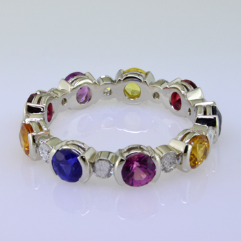Want to brighten your day?  This amazing band will do it.  Feel special with this one of a kind eternity band with multi color sapphire gemstones.  All the colors of the rainbow,  This eternity band has .46ct. of sparkling diamonds and is surrounded by 9-round colorful sapphires.  This beautiful ring is made to order,so please allow 3-4 weeks for us to make it just for you. Call us for pricing.  Designed and created by master jeweler Stuart J.