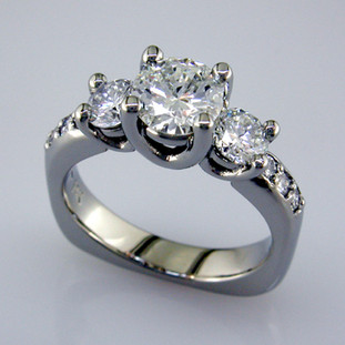 This beautiful diamond engagement ring design with its simple, clean lines frames your diamond perfectly. The bottom has soft rounded corners for the ultimate comfort. This is a vintage inspired, but timeless design.    This elegant diamond engagement ring is priced in 14k white gold, and can be made in any karat or color of gold, and in platinum. Set with .59ct. of ideal cut diamonds, this one is shown with a 2 carat brilliant round cut center (sold seperately), but we will make it for any size. A matching shadow wedding ring or a diamond wedding ring is available.(sold seperately)  This custom designed engagement ring is individually crafted to be Perfectly You, and takes about 2 weeks to create. Call us for more information about how we can customize this design Just For You. Designed, and created in our studio by the artist Stuart J.