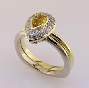 Here is a diamond halo engagement ring with a sophisticated flare. Custom designed with .20ct. T.W. of pavé set ideal cut diamonds makes this ring sparkle like crazy. A beautiful .28ct. Pear shaped natural color golden yellow diamond is the focal point of this double row pavé halo. It is set in a green gold bezel to accentuate its vivid color, and makes it look larger than it is. And not a single prong to worry about! This pavé diamond engagement ring feels smooth and is easy to wear. It is hand made in 14 karat white gold, with a 14 karat Green gold accent border around the diamonds. You will love the custom touches on this sweet engagement ring, like the beautiful open design on the underside. A matching wedding ring in 14 karat green gold is shown, and compliments the set perfectly. (Priced seperately)   As with all of our designs, we will make this any way you like, with any gemstones you like.  Custom designed and hand crafted in our studio by the artist Stuart J.