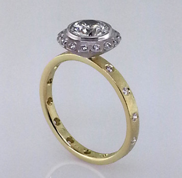 This contemporary halo engagement ring with old world charm has a sophisticated flare. It's hand crafted in rich 18 karat yellow gold, and set with .21ct. total weight of brilliant cut diamonds, and a beautiful .84ct. round brilliant cut diamond in a white gold flower bezel. You can feel the beauty and elegance of this ring the moment you put it on.  Designed by the acclaimed artist Alishan in his California studio. All designs can be made any way you like, with any gemstones you like.