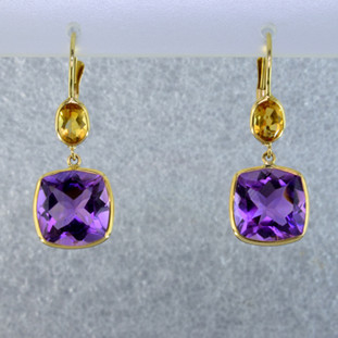 Beautiful delicate drop dangles you can wear day or night. 14 karat yellow gold with antique cushion cut amethyst gemstone and a pear shaped citrine gemstone hanging above. hangs on lever backs and measures 1 inch long.