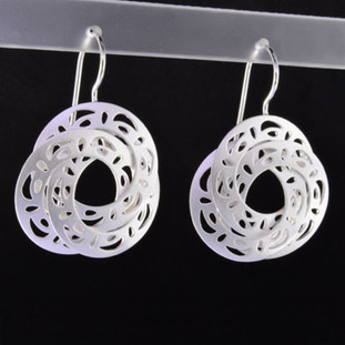 Playful and bright, these triple circle open filagree dangle earrings are a delight to wear and they will make you smile. Crafted in Sterling Silver with a floral pattern, hanging on wires, and measuring 1 3/4 inches long.   Handmade in Istanbul, Turkey.