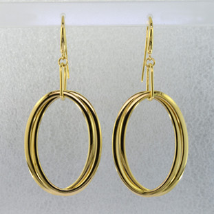 These earrings are sure to make you feel good. Edgy and modern double tier oval hoop earrings in 14 karat yellow gold. Hanging on gold wires, these earrings measure 2 1/4 inches long.
