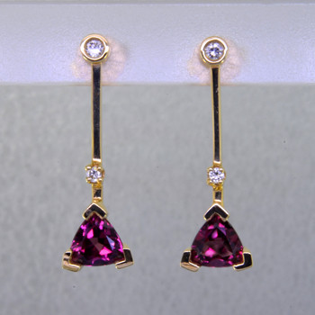 "Fun and modern, these earrings dazzle for day or night. Hand crafted in 14 karat yellow gold with sparkling 6mm rhodolite garnet trillian gemstones and .10ct. of ideal cut diamonds hanging on posts.. Earrings measure 1"" long.    Designed, and created in our studio by the artist Stuart J."