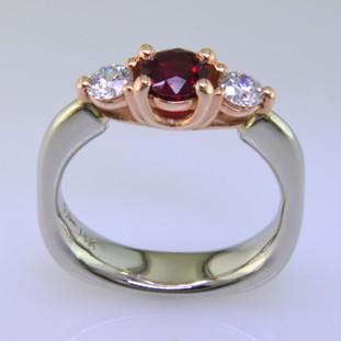 This delicate 3-stone ring is magical. 14 karat White Gold ring shaped with a soft square at the bottom, and 14 karat Rose Gold woven prong work on top. It feels soft and comfy on your finger. Set in the center is a .59ct. beautiful red ruby gemstone, and the sides total .34ct T.W. Ideal cut Diamonds.  Finger size 6 1/2. Can be sized, or custom made in your size. By special order only.  Please allow 4-6 weeks.  Designed, and created in our studio by the artist Stuart J.