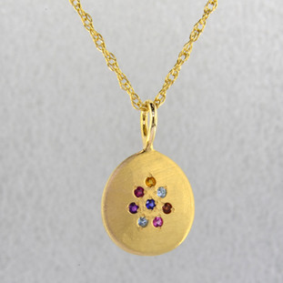 "This sweet pendant shimmers when you wear it. Beautiful 14 karat yellow gold medallion sprinkled with aquamarine,ruby,garnet,amethyst,pink tourmaline, and blue zircon gemstones set in a starburst pattern, with a blue sapphire in the center, hanging on a 1.3mm rope  chain. 18"" long.    Wear it as a birthstone pendant too, and customize it just for you.  Call for prices on your special birthstones. Special orders will take 2-3 weeks  Designed and created in our studio by the artist Stuart J."