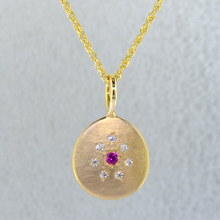 This sweet pendant has a special, hand applied finish that shimmers when you wear it. Beautiful and rich 14 karat yellow gold drop, sprinkled with .06 carat total weight of ideal cut diamonds, with a glowing pink sapphire gemstone in the center. Comes with an eighteen inch, 14 karat yellow gold rope chain. Pendant measures 5/8 inches long.    Designed and created in our studio by the artist Stuart J.