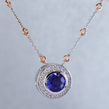 "Modern and timeless blue sapphire halo pendant, thoughtfully crafted in recycled 14 karat white gold will light up the room! Set with .29 carat total weight of super sparkly Ideal cut diamonds, and an incredible 2.87 carats natural Ceylon blue sapphire gemstone. This sapphire and diamond pendant has no prongs to worry about, and can be dressed up or down to go with any outfit. Dress it up with the included 14 karat white gold diamond station chain with rose gold accents, with a third carat of diamonds, measuring 18"" long. A truly spectacular piece, that will never be out of style!  Designed, and created in our studio by the artist Stuart J."
