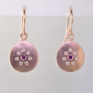 These sweet earrings shimmer when you wear them. Beautiful and warm 14 karat rose gold medallion drops sprinkled with .11ct. of ideal cut diamonds set in a starburst pattern, with a glowing pink sapphire in the center, hanging from wires. 12mm long.    Designed and created in our studio by the artist Stuart J.