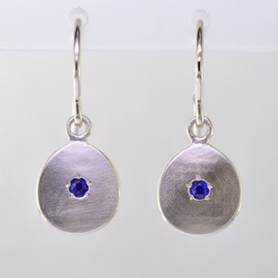 These sweet gemstone earrings shimmer when you wear them. Beautiful in 14 Karat white gold, these medallions with dreamy blue sapphire gemstones in the center, hanging from 14 karat white gold wires.  Earrings measure 3/4 inch long. Available in other colors. Please call for pricing.  Designed and created in our studio by the artist Stuart J.