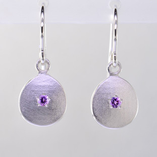 These sweet gemstone earrings shimmer when you wear them. Beautiful in Sterling silver, these medallions with bright amethyst gemstones in the center, hanging from sterling silver wires.  Earrings measure 3/4 inch long. Available in other colors. Please call for pricing.  Designed and created in our studio by the artist Stuart J.