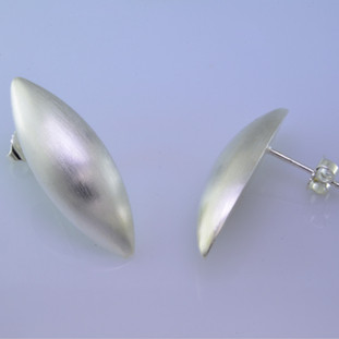 Sleek and modern, these pod earrings are beautiful and elegant.  Easy to wear from day to night. Sterling silver with a smooth finish, and hangs on a post. Earrings measure 1 1/4 inches long.  Made in Istanbul, Turkey.