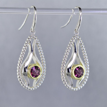 You will be captivated by this mix of modern and vintage in these elegant earrings.  The mix of sterling silver and 18K green gold is magical as these earrings comes together. The 18K bezels make these 6mm rhodolite garnet stratus gemstones pop as they are smooth and have a beautiful deep reddish color.The blend of the two metals is sophisticated, and fun, all at the same time. Perfect for any time of the day or night. These earrings hangs on sterling silver ear wires. The earrings measure 1 1/2 inches long.  Designed, and created in our studio by the artist Stuart J.