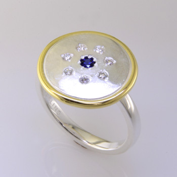 This sweet ring has a special, hand applied finish that shimmers when you wear it. Crafted in beautiful sterling silver, and framed in rich 18 karat yellow gold. It is sprinkled with 7 ideal cut diamonds weighing a tenth of a carat, with a Chatham® created deep blue sapphire gemstone in the center. This one is a size 7, but we can make it in any size. Ring top measures 5/8 inch in diameter.    Chatham Gemstones are also available in Ruby, Sapphire, and Alexandrite.  Designed and created in our studio by the artist Stuart J.  Chatham® Created Gemstones are grown in carefully controlled laboratory conditions. They are chemically and optically identical to their natural counterparts, yet cost much less. Because the environment in which they are grown is controlled, the imperfections often found in natural gemstones, are absent in Chatham® Created Gemstones. Because of this, and superior cutting, Chatham® gems exhibit the color and sparkle of the finest natural gems. Each one comes with a Certificate of Authenticity, and a Lifetime Warranty.