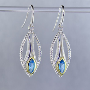 You will be captivated by this mix of modern and vintage in these elegant earrings.  The mix of sterling silver and 18 karat green gold is magical as these earrings comes together. The 18 karat bezels make these beautiful 8x4mm marquise, sea blue color, Swiss blue topaz gemstones pop! The blend of the two metals is sophisticated and fun, all at the same time. Perfect for any time of the day or night. These earrings hang on heavy sterling silver ear wires, and measure 1 1/2 inches long.  Designed and created in our studio by the artist Stuart J.